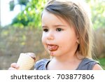 little girl eating ice cream... | Shutterstock . vector #703877806