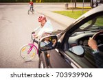 Small photo of Accident. Small girl on the bicycle crosses the road in front of a car
