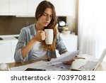 serious young housewife in... | Shutterstock . vector #703970812