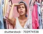 femlae seller in clothes shop... | Shutterstock . vector #703974538
