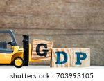 Small photo of Toy plastic forklift hold block G to compose and fulfill wording GDP (Gross domestic product or Good distribution practice) on wood background