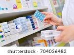 pharmacist holding medicine box ... | Shutterstock . vector #704036482