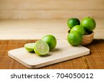 lime slices on wooden chopping... | Shutterstock . vector #704050012