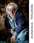 Small photo of Nomad Valley, Morocco - January 18, 2016: Nomad man sitting in the cave that is his home. Even now some Berber families are living traditional way.
