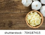mashed white garlic in wooden... | Shutterstock . vector #704187415