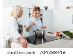 happy young woman cooking...   Shutterstock . vector #704288416