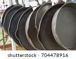 Small photo of Hanging row of cast iron skillets at swap meet