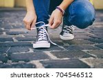 a woman binds laces on her...   Shutterstock . vector #704546512