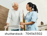 cheerful friendly nurse helping ... | Shutterstock . vector #704565502