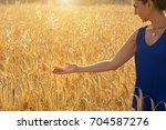 girl in blue dress touching a... | Shutterstock . vector #704587276