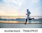 a handsome young man running in ... | Shutterstock . vector #704619925