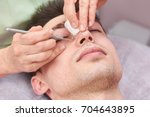 cosmetician cleaning face close ... | Shutterstock . vector #704643895