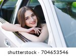 a young girl is driving a car. | Shutterstock . vector #704653546