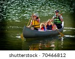 Family In A Canoe On A Lake In...