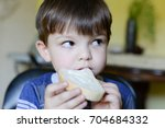 boy eating bread with cream... | Shutterstock . vector #704684332
