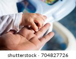 baby holding hands with father