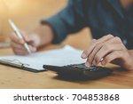 man using calculator and... | Shutterstock . vector #704853868