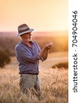 a farmer standing in his cereal ... | Shutterstock . vector #704904046