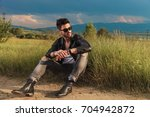 seated man wearing leather... | Shutterstock . vector #704942872