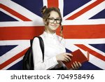 Small photo of Pretty young girl with book over English flag. Learning and study concept.