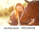girl hugging with a horse at... | Shutterstock . vector #705135418