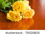 three yellow roses on wood table - stock photo