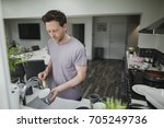 man is washing the dishes in... | Shutterstock . vector #705249736