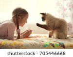 Stock photo cute girl with pigtails plays with a cat 705446668