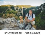 Stock photo hiker and his small yellow dog sitting on the mountain top and resting 705683305