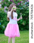 Small photo of Beautiful little girl is playing with soap bubbles. Carefree childhood.