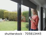 woman is looking out of her... | Shutterstock . vector #705813445