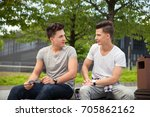 two friends sitting on bench in ... | Shutterstock . vector #705862162