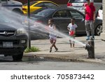boys play in water spray from a ...