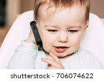 happy baby holding smartphone.... | Shutterstock . vector #706074622