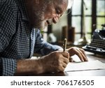 Stock photo closeup of senior man writing letter 706176505