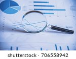 Small photo of Accounting data, charts and magnifying glass. Many charts and graphs. Reflection light and flare.