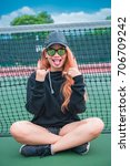 Small photo of Cool Hipsters girl in black hood with black hat and black sunglass,lifestyle of teenage,thailand people,young woman posing on couse of tennis