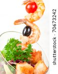 Fried kebab of shrimps with vegetables, greens and salmon fish - stock photo