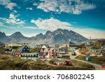 Picturesque village on coast of Greenland with mountains in background