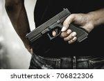 a man holding a gun in hand ...