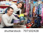 Stock photo happy young boyfriend helping girl to choose bowl in pet store focus on guy 707102428