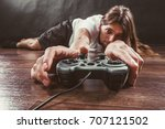 Small photo of Addiction and dependency concept. Young man with pad joystick playing games. Male addicted to console videogames.