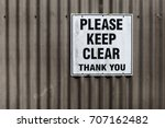 Small photo of please keep clear sign on a corrugated iron garage door background