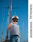 Small photo of happy little boy wearing captain hat and sailor striped shirt aboard recreational boat in summer sunny day