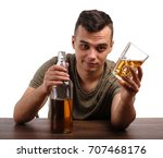 Small photo of A male in a green T-shirt is showing a bottle and a glass full of whiskey or liquor, isolated on a white background. A boozed guy holding a full glass of alcoholic drink. Alcoholic addiction concept.