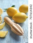 Small photo of Ripe lemons and wooden citrus reamer on table, closeup