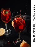 Small photo of Two glasses of sangria with citrus and fresh mint. Splash of drink. Black background. Close up.