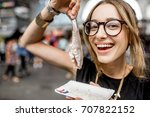 Stock photo young woman eating herring with onions traditional dutch snack in rotterdam market 707822152