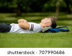Teenage boy laying on grass on a summers day - stock photo