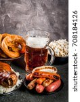 Small photo of Selection of traditional German food Oktoberfest. Beer, baked pork shank, popcorn, assortment of different sausages, homemade bretzels. On a black stone background copy space